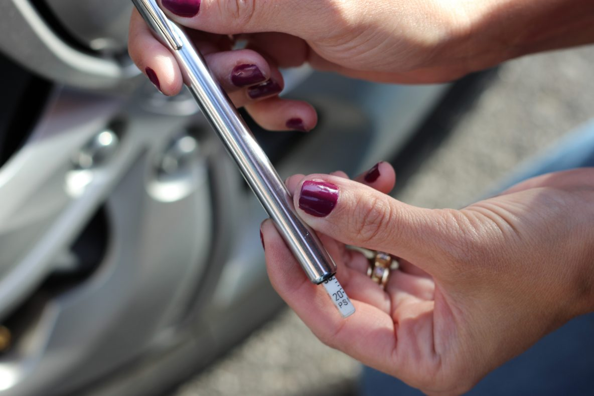 image of how to check tire pressure with a pressure gauge