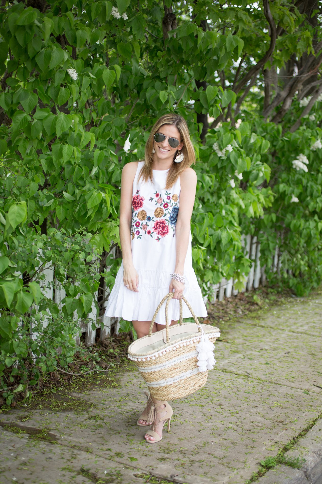 Zara white embroidered dress, nude heels, straw tassel bag, silver Ray-Ban aviators